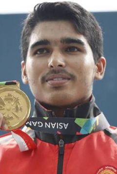 Gold medalist India's Saurabh Chaudhary, poses for photographers after the 10m air pistol men's final shooting event during the 18th Asian Games in Palembang, Indonesia, Tuesday, Aug. 21, 2018. (AP Photo/Vincent Thian)